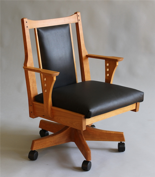 The Swivel Desk Chair With A Shorter Back Rest And In Black Leather Upholstery