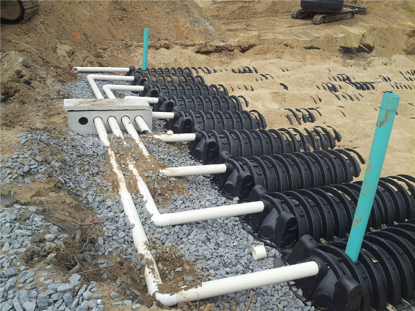 Installation of 9 rows of Quick 4 Infiltrators Chambers-close up shot of stone splash pad per engineer's plans