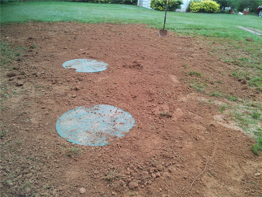 Final grading showing the locking lids of the two compartment Infiltrator Septic Tank. This installation was completed by A-Norton Septic on a rainy day. Entire job start to finish was completed in one day including Health Department inspections. Got Septic? Get A-Norton Septic!