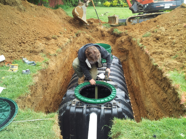 Installation of an Infiltrator Septic Tank. Note the two lids as this tank is a two compartment tank that allows for further filtration of effluent that leaves the tank to the disposal area.