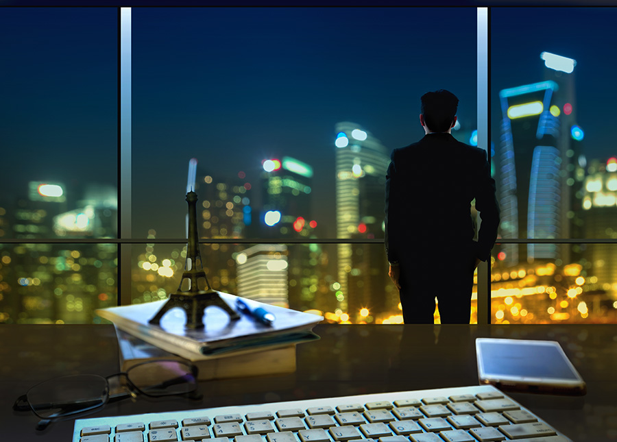 Man standing over nighttime city with keyboard and phone showing on desk