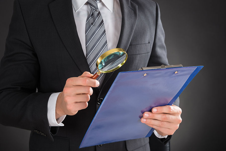 Man holding magnifying glass against document