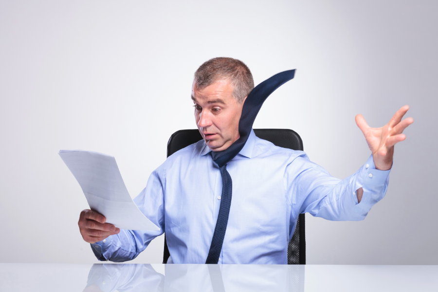 Man looking shocked holding a piece of paper