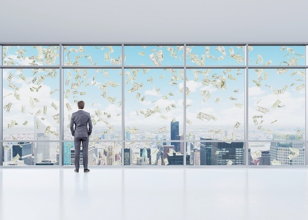 Man looking outside of window at a city with money in the sky