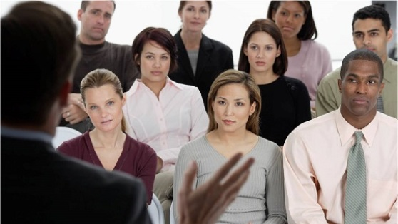 Photo of an attentive audience at a public speaking event.