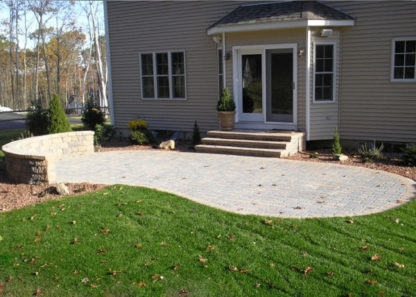 Small paver patio with a sitting wall by bahler brothers