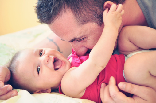 Father playing with his happy and smiling baby daughter