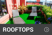 artificial grass on a rooftop with chairs on it