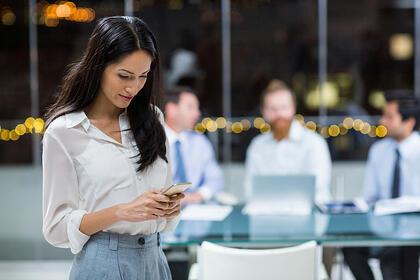 Businesswoman text messaging on mobile phone in the office-1