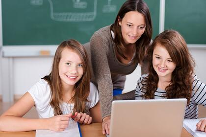 Cheerful teacher teaching her two students with laptop inside the classroom
