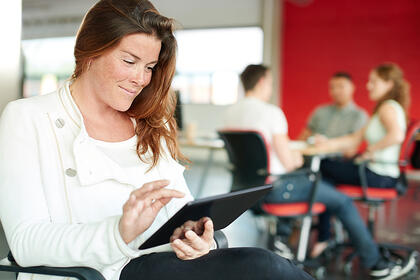 Confident female designer working on a digital tablet in red creative office space-3