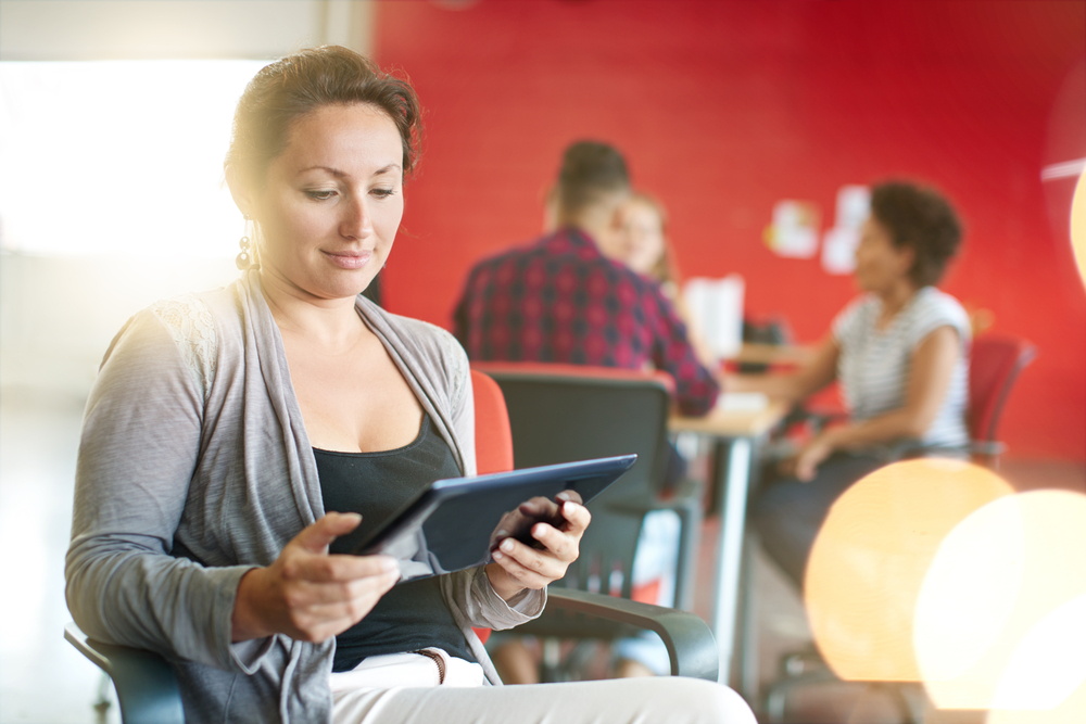 Confident female designer working on a digital tablet in red creative office space-4