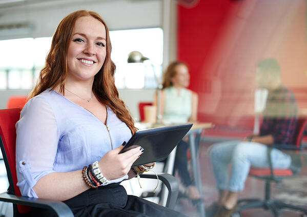 Confident redhead female designer working on a digital tablet in red creative office space-1