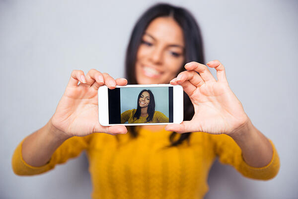 Happy woman making selfie photo on smartphone over gray background. Focus on smartphone