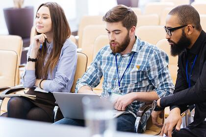 Multiethnic group of young business people using laptop sitting on meeting in conference hall