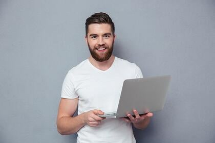 Portrait of a smiling casual man holding laptop over gray background