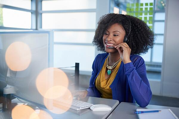 Portrait of a smiling customer service representative with an afro at the computer using headset-1