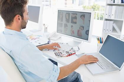 Side view of a male photo editor working on computer in a bright office