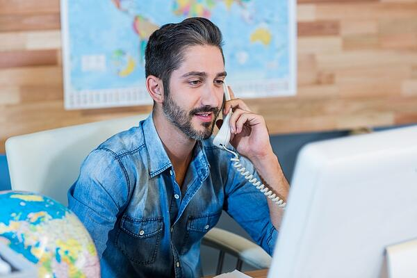 Smiling travel agent having phone call in the office