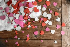 Cut out hearts in red, pink, and white for Valentine's Day