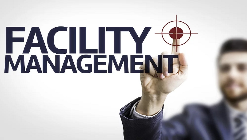 Business man pointing to transparent board with text Facility Management