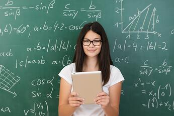 Clever attractive young female college student wearing glasses and holding a tablet computer in her hands standing in front of a chalkboard covered in equations in maths class smiling at the camera