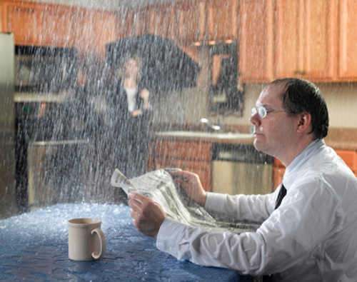man drinking coffee in kitchen while it rains inside due to leaky roof