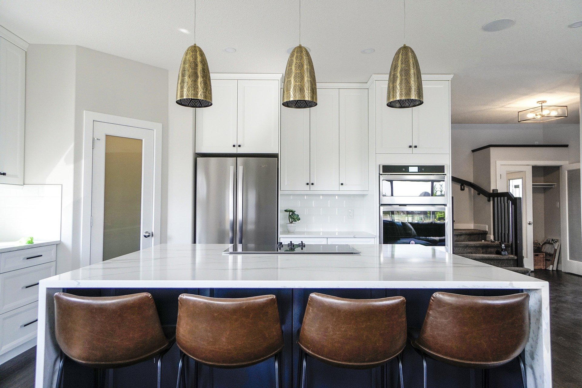 transitional white kitchen white slab quartz island