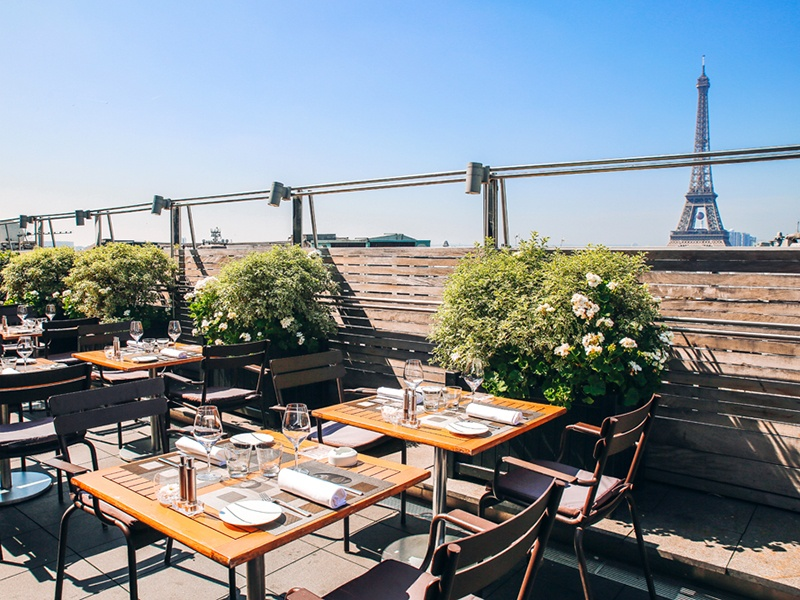 The terrace of Maison Blanche, perched on the rooftop of Théâtre des Champs-Elysées, overlooks the Eiffel Tower and the streets of Paris below. Banner image: The gilt moldings, exquisite frescoes, and sparkling chandeliers of Le Train Bleu will transport diners to the early 1900s.