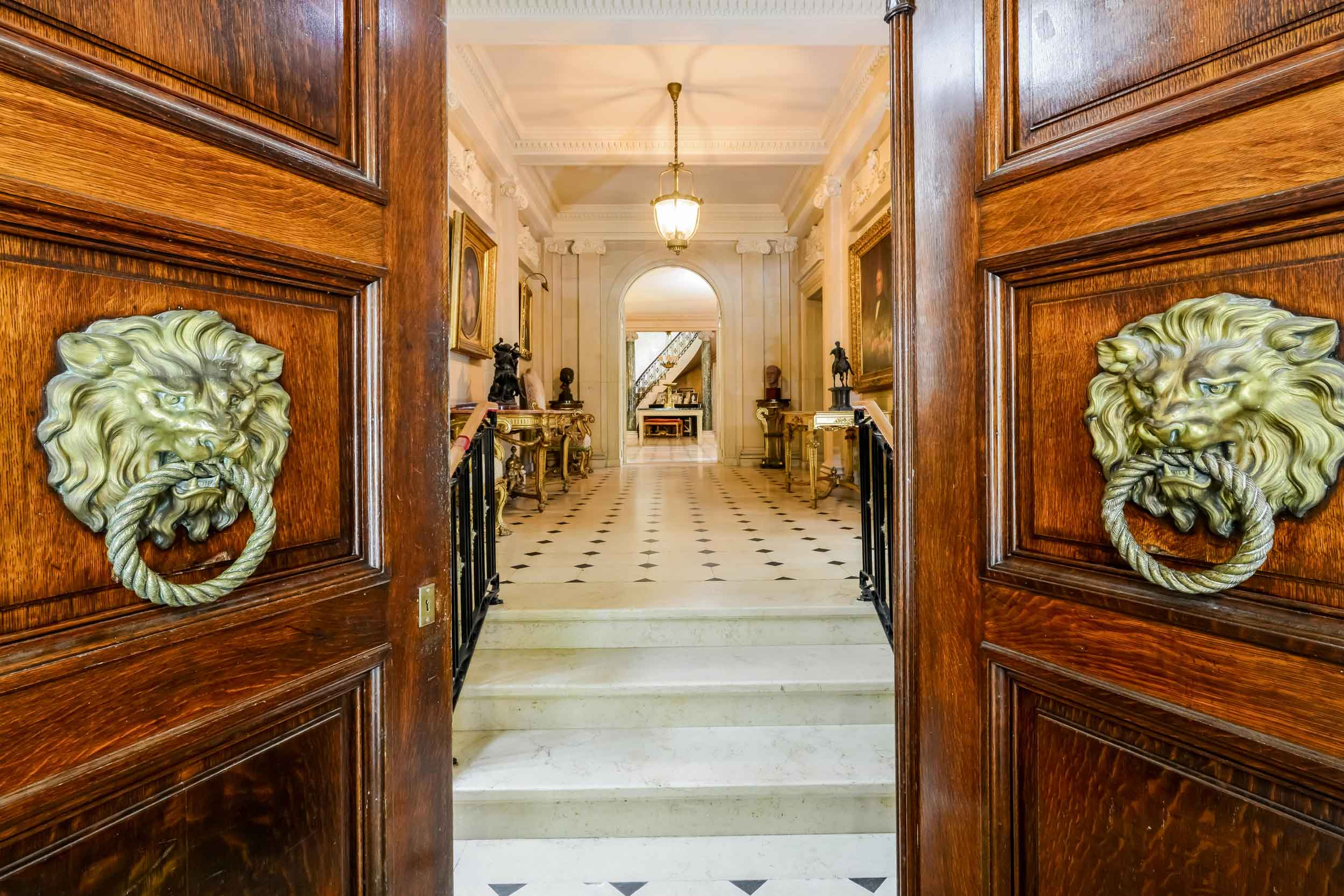 Monumental mahogany doors with antique bronze door knockers in the shape of a lion's head open to the mansion's palatial living areas, measuring 13,962 square feet, with 11 bedrooms, eight full and three half bathrooms.