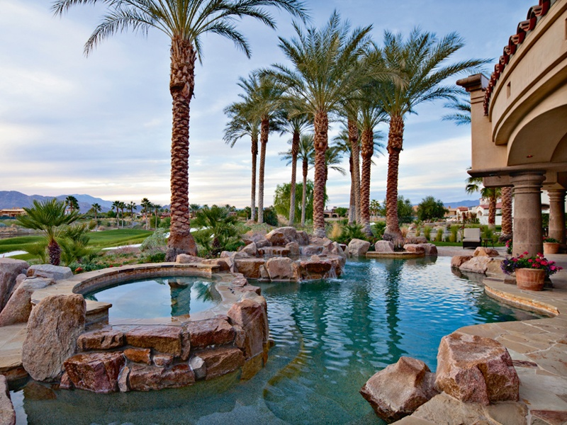 Custom stonework at this property in La Quinta, California, mirrors the mountain backdrop—notably in the outdoor living area, featuring a pool with waterfalls, a raised spa, and ponds. On the market with HK Lane Real Estate, Inc., the region's exclusive affiliate of Christie's International Real Estate.