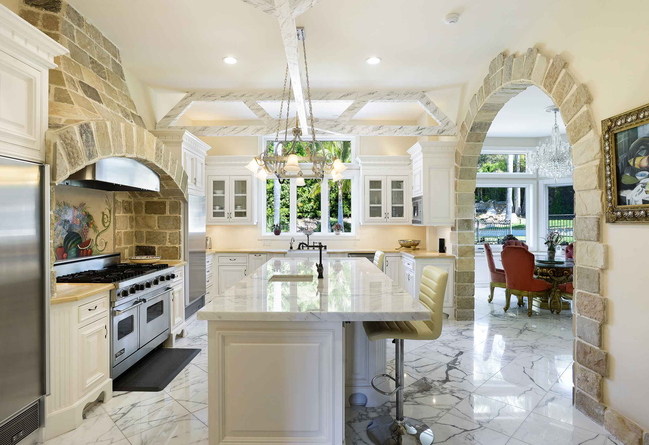 Serving the breakfast nook is a fully equipped chef's kitchen, complete with center island/breakfast bar, sandstone walls, and white marble floors.