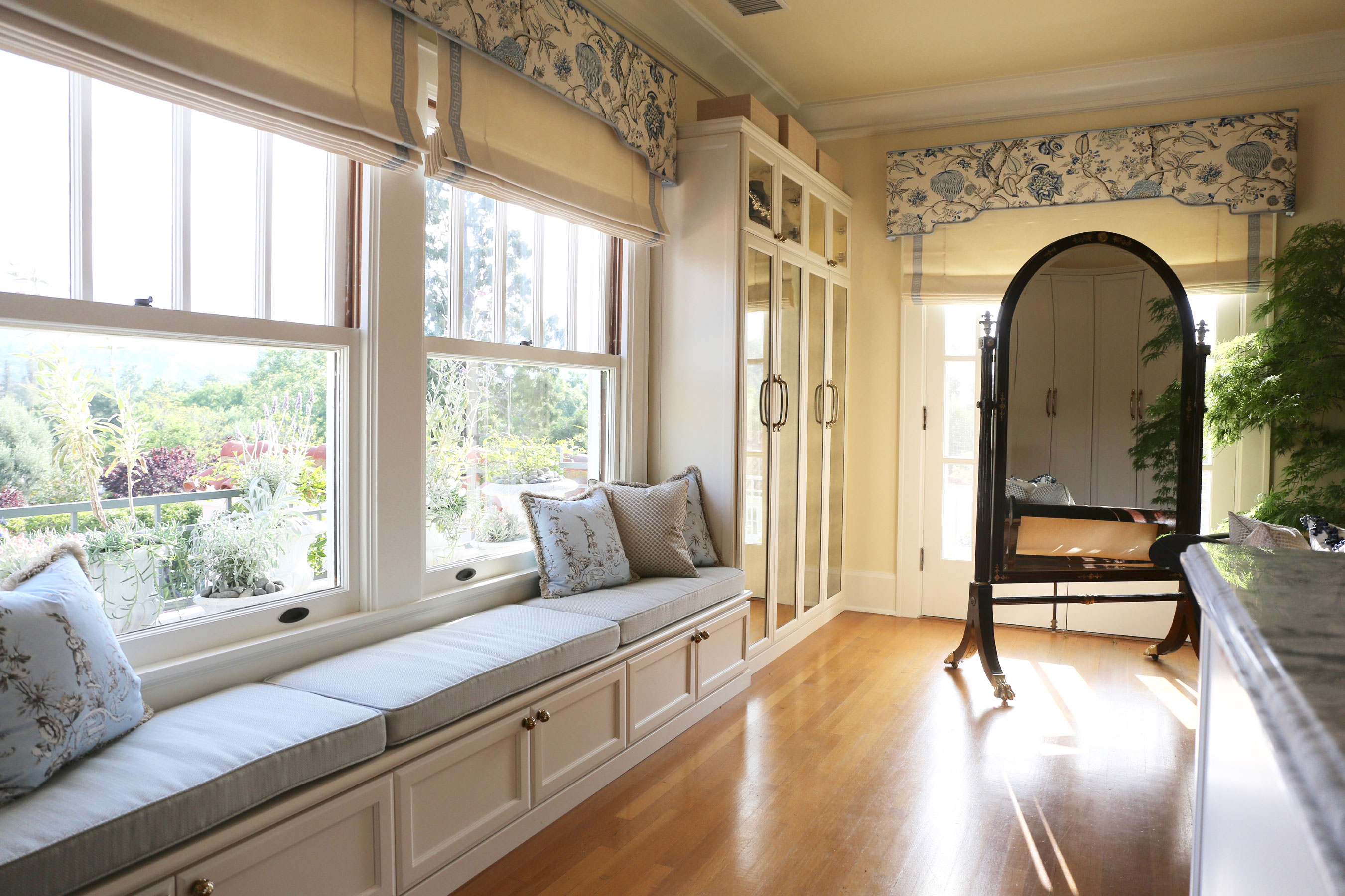 This California home's walk-in wardrobe and dressing room is appointed with custom-designed built-ins including several closets, a center island, and banquette; chandeliers and huge windows provide ample light.