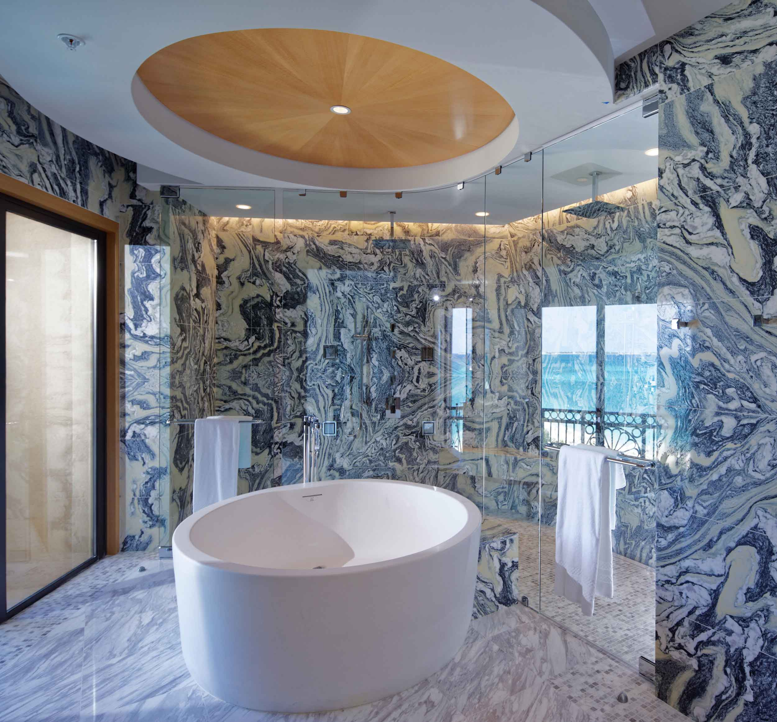 One of the finest beaches in the Caribbean (Grand Cayman's Seven Mile Beach) is on full display from the master bathroom of this ultra-luxury penthouse atop the Ritz-Carlton Grand Cayman. The bespoke finishes were designed to complement the beauty of the home's tropical environment, and include a huge walk-in rainforest shower in blue marble tile, a soaking tub, and televisions built into the mirrors.
