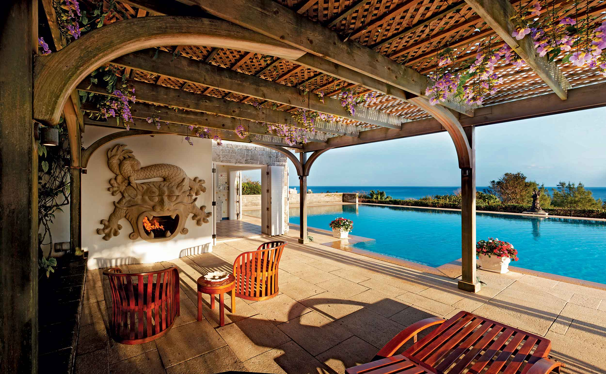 A rare Chinese stone fireplace in the shape of a five-armed dragon forms the centerpiece of the pergola, which faces the infinity pool and the Atlantic Ocean beyond.
