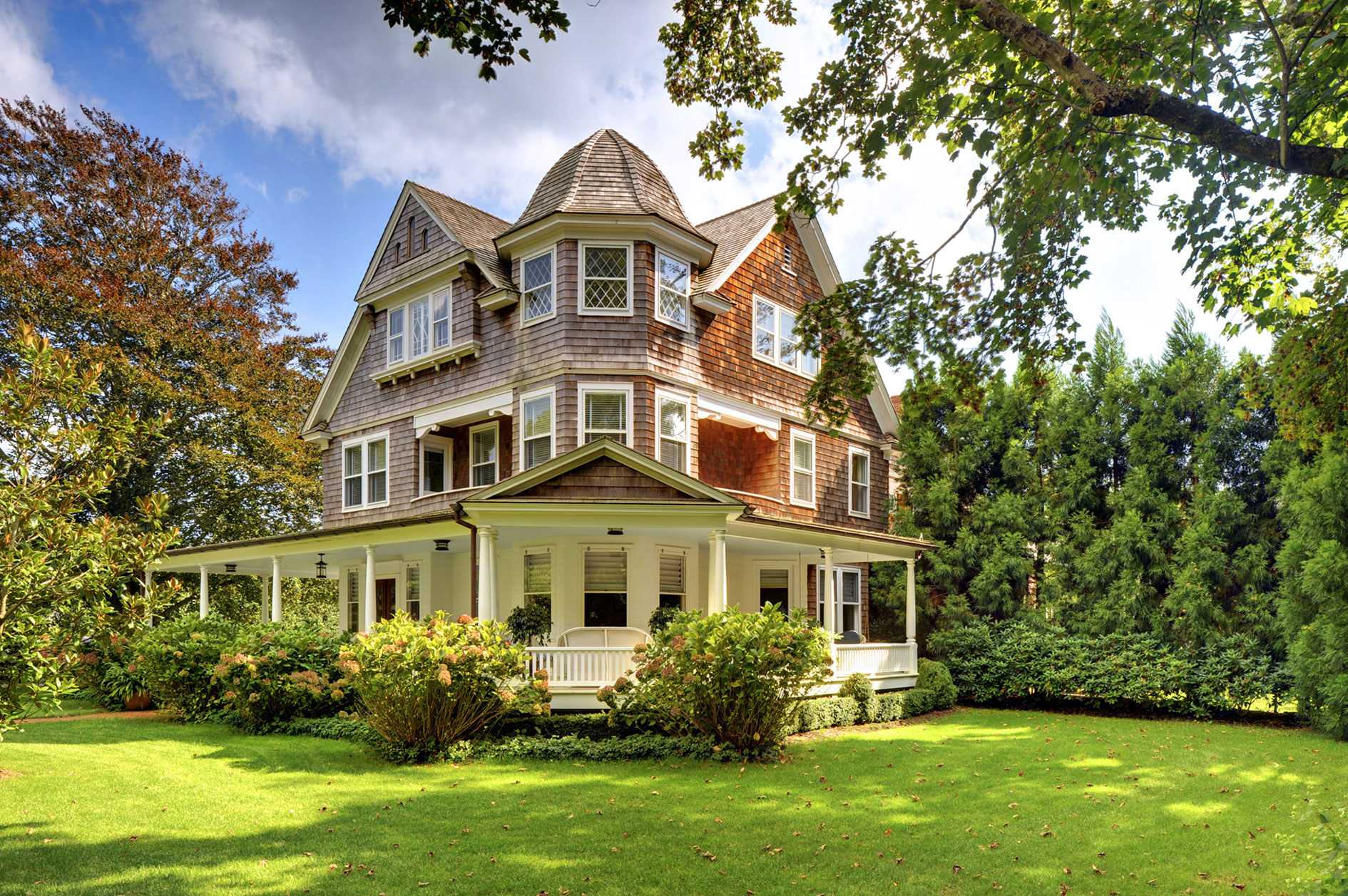 This home's striking architectural features are a testament to the late Queen Anne Revival style of the Northeast. Its shingle façade, asymmetrical roofline, and wraparound porch are among the classic details.