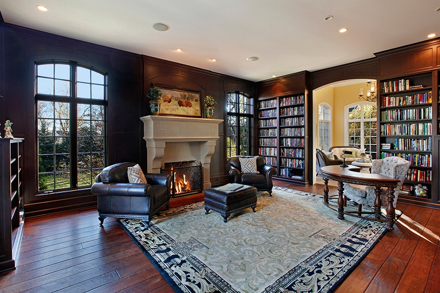 This intimate library features a grand fireplace, a view of the grounds, and an adjoining sitting room suffused with natural light.