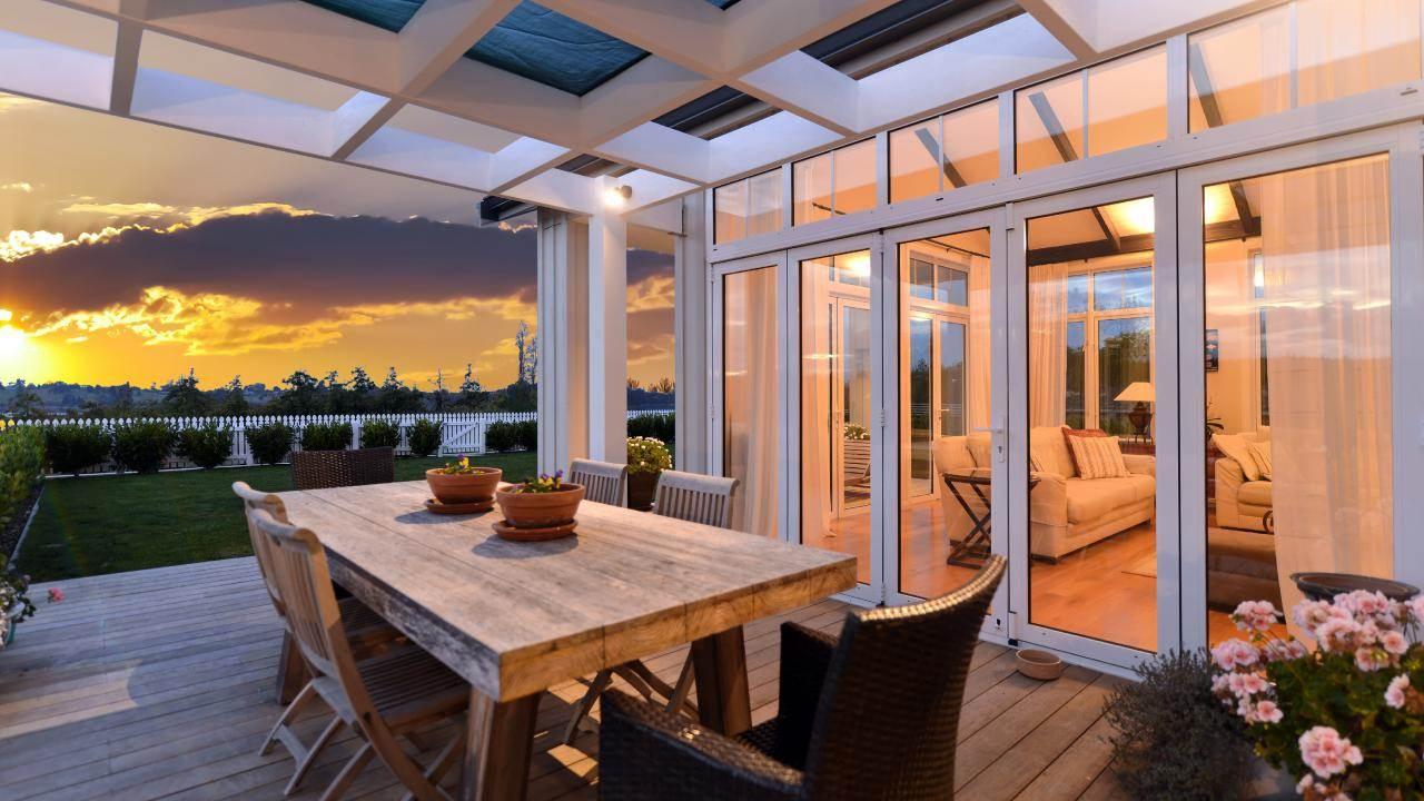 The sun's rays illuminate this award-winning New Zealand home's outdoor deck that enjoys views of snowcapped Mt. Arthur.