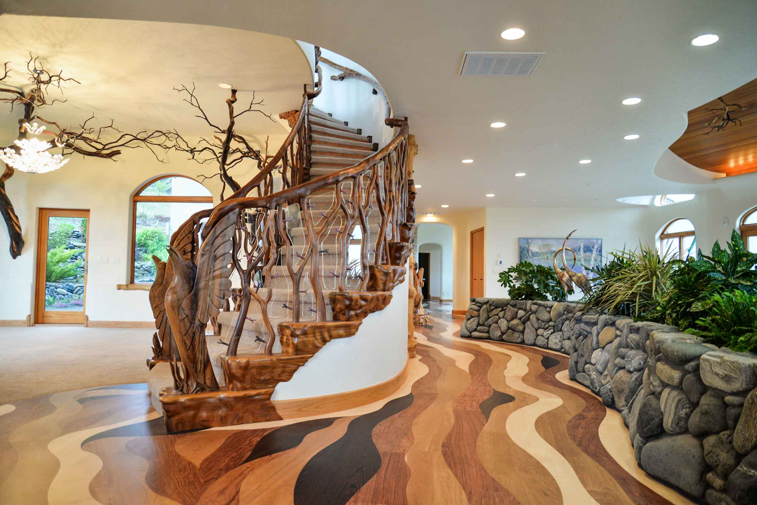 The foyer is one of a kind. The granite floor is reminiscent of the sandy shore at the edge of a river. Above, the ceiling is tiled in blue stone to resemble the sky.