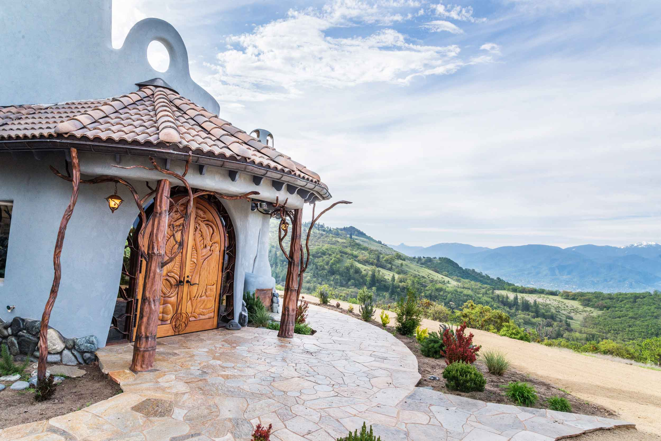 The entrance to this unique 700-acre estate is marked by arched front doors framed by beautiful copper tree sculptures. Their branches extend out to intertwine and support the covered entryway. Other doors throughout the home pay homage to the native cultures, plants, and animals indigenous to the region.