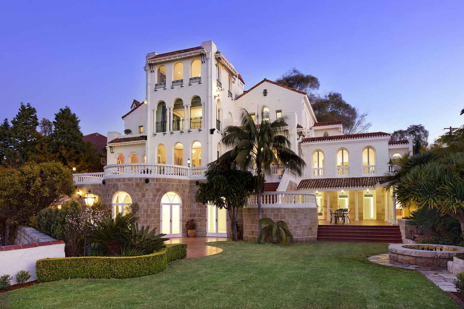 Alcooringa, a magnificent 1930s Spanish Mission-style estate, has a prime location in Bellevue Hill with convenient access to Sydney CBD, Sydney Opera House, and the theater district. The property includes a seven-bedroom main residence, a three-bedroom cottage, a private chapel, and landscaped gardens overlooking Sydney Harbour, North Head, and the Pacific Ocean.