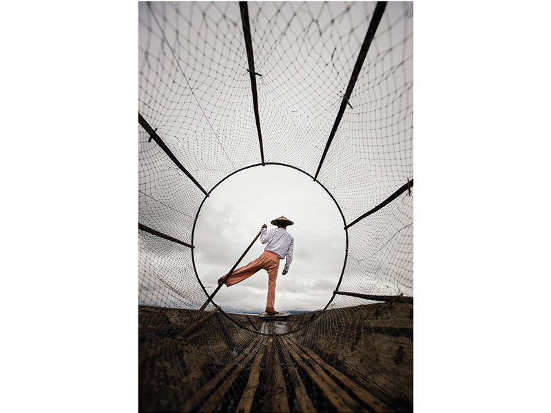 A unique perspective, looking through the basket net of a fisherman on Inle Lake in Shan State, Myanmar. Photograph: ©Drew Hopper Photography