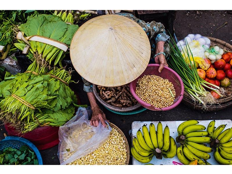 A street vendor sells fresh fruit and vegetables in Hội An, Vietnam. Photograph: ©Drew Hopper Photography