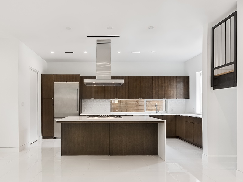 In this modern home at 4710 La Branch Street, a spacious open floor plan leads to a kitchen outfitted with stainless-steel appliances, custom cabinetry, a wine cooler, quartz counters, and an oversized island. Photograph: Nan and Company Properties