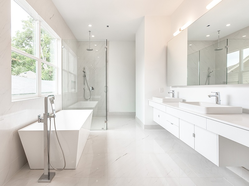 The home is distinguished by its white Spanish Porcelanosa tile, recessed lighting, and large windows that allow sunlight to illuminate the bright walls and sleek fixtures. Photograph: Nan and Company Properties