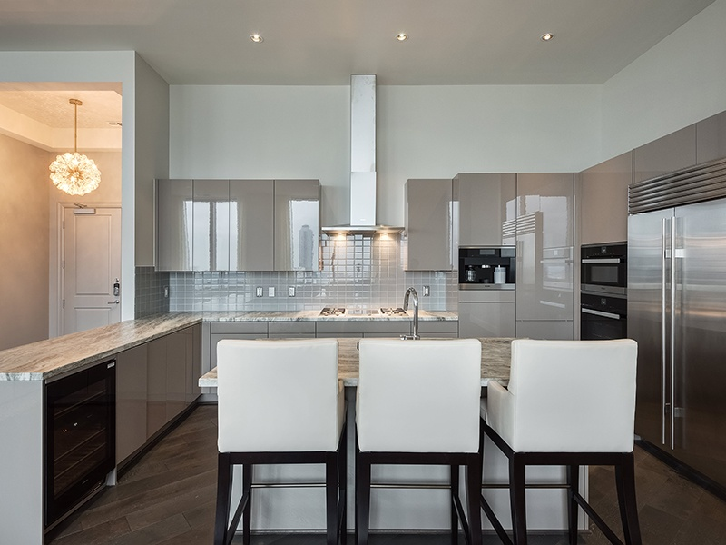 The gourmet kitchen, outfitted with leathered marble countertops, sleek cabinetry, stainless-steel Miele appliances, and a breakfast bar, flows into the dining area and family room. Photograph: Nan and Company Properties