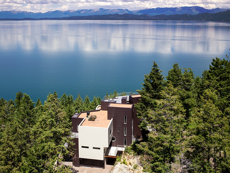 Nestled into the hillside above Flathead Lake in Rollins, the contemporary Wildwood Ridge property represents a reversal from the raw wood and stone characteristic of the Mountain Modern style. Photograph: PureWest Real Estate