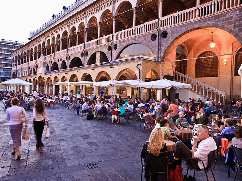 The piazzas flanking Palazzo della Ragione in Padua offer a range of cafés and restuarants, as well as market stalls selling fruit, vegetables, and local specialties. Photograph: Getty Images