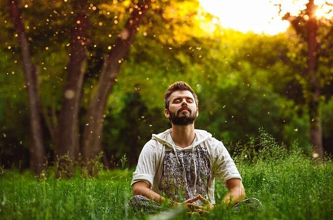 man-meditating-on-green-grass-1024x678