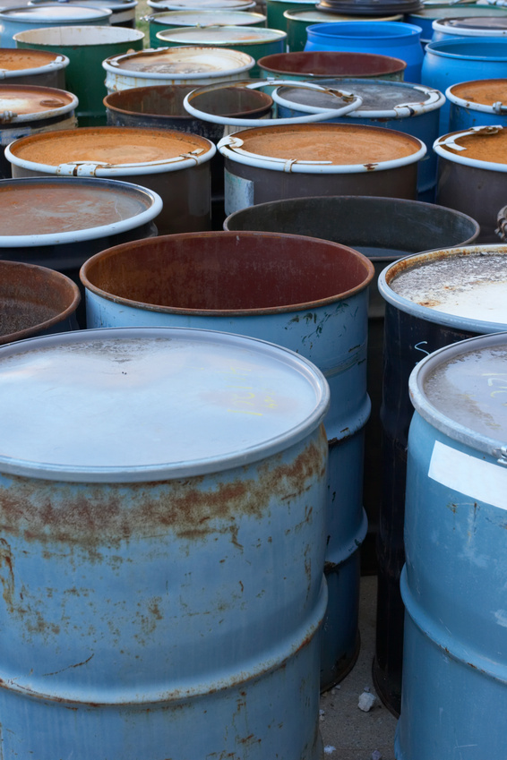 drums of hazardous waste, some with chemical labels.